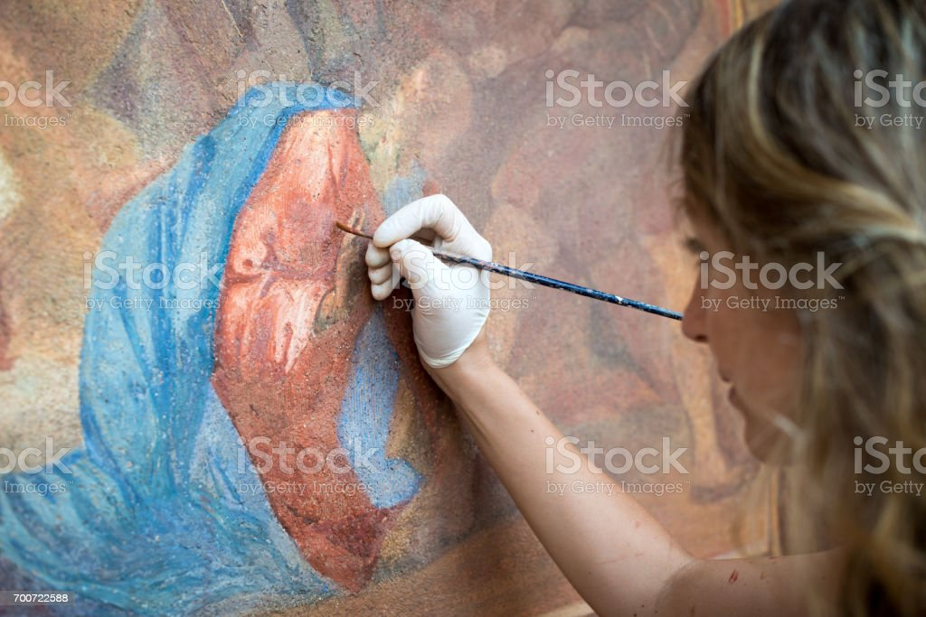Restorer working on antique outdoor chapel fresco in Italy: Painting restoring of religious art stock photo