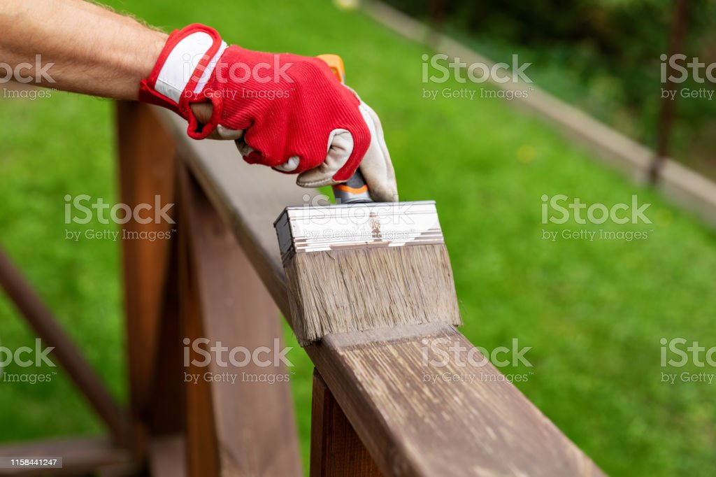 restoring wood protective paint on outdoor patio railings