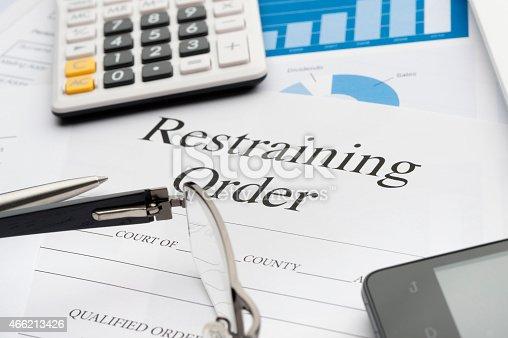 Restraining order form on a desk. Restraining order form on a desk with a calculator, pen, glasses, mobile phone and digital tablet.