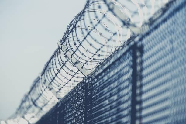 clôture de fer barbelé de zone réglementée - prison photos et images de collection