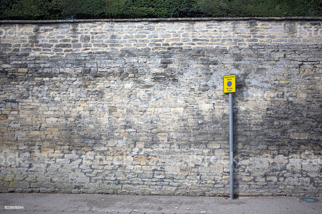 restricted parking zone sign against a large wall stock photo