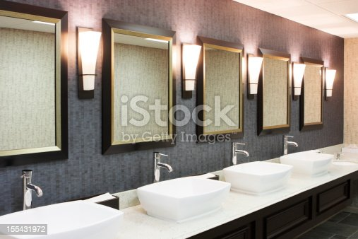Sinks, faucets, mirrors and lighting sconces in a luxury hotel restaurant restroom.