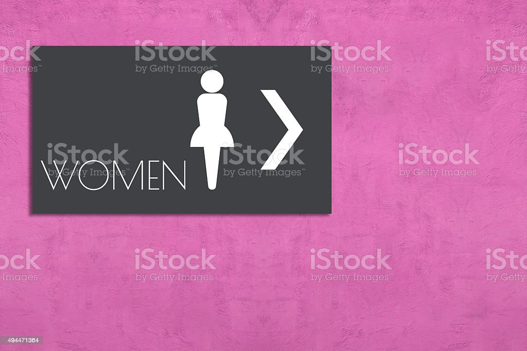 restroom sign on pink wall stock photo