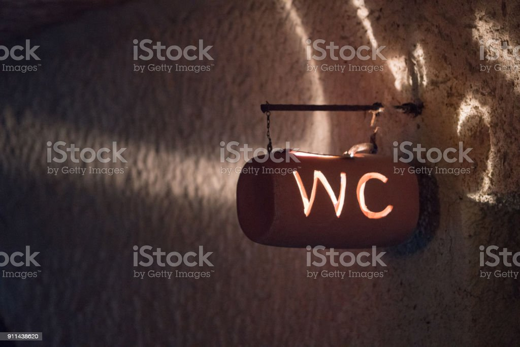 Restroom sign on stone wall background stock photo