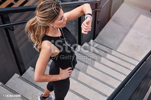 High angle shot of a sporty young woman checking her watch while exercising outdoors