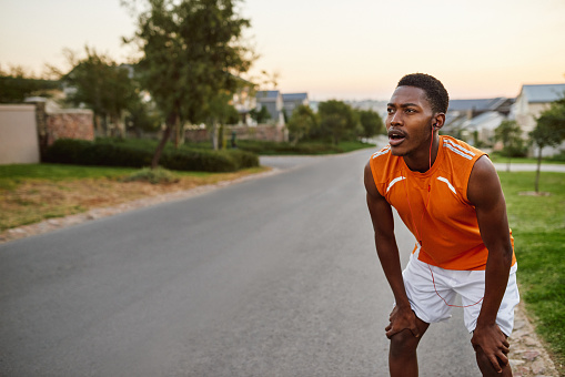 Shot of a sporty young man taking a break while exercising outdoors