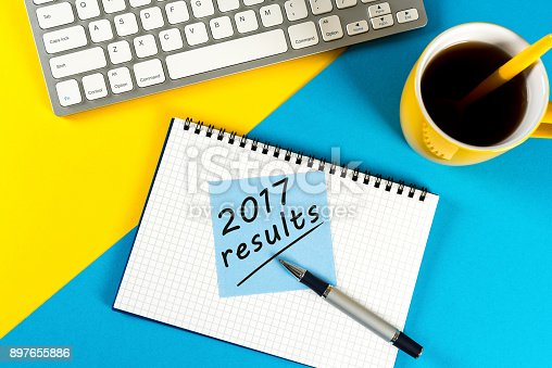 897644798istockphoto 2017 results - note at blue and yellow workplace with coffee. Time to annual review 897655886