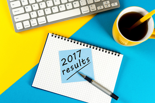 897644798 istock photo 2017 results - note at blue and yellow workplace with coffee. Time to annual review 897655886