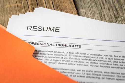 Stock photograph of job resume inside orange folder.
