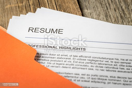 Stock photograph of job resume inside orange folder.