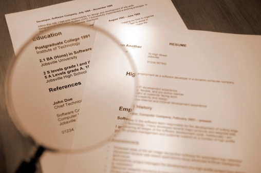 sepia toned selective focus shot of resume and magnifying glassPlease Note: All information on resume is fake
