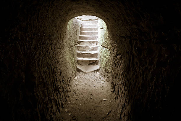 Resurrection From The Darkness Light at the end of the tunnel. Dark stone room with a stairway encased in sunlight. tomb stock pictures, royalty-free photos & images