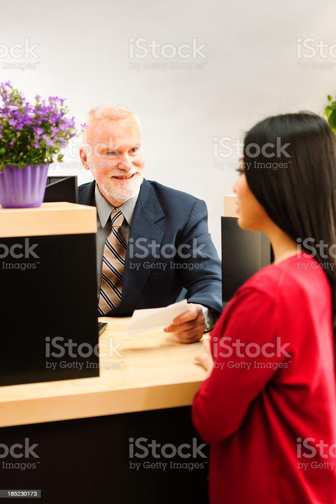 A Caucasian man retail bank teller in business suit providing...