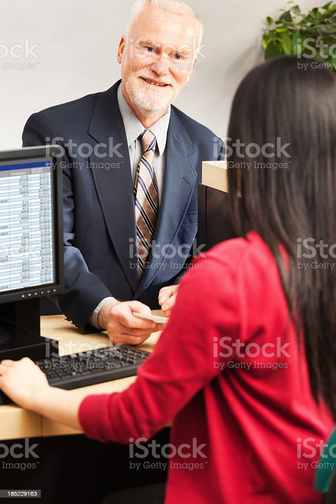 A young Asian bank teller working at the work station of a bank...