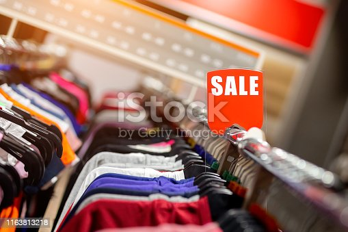 Retail clothes store clearance. Garment shop with various bright youth casual wear at discount price. Wear hangers and red SALE signboard. Seasonal sales on fashion market.