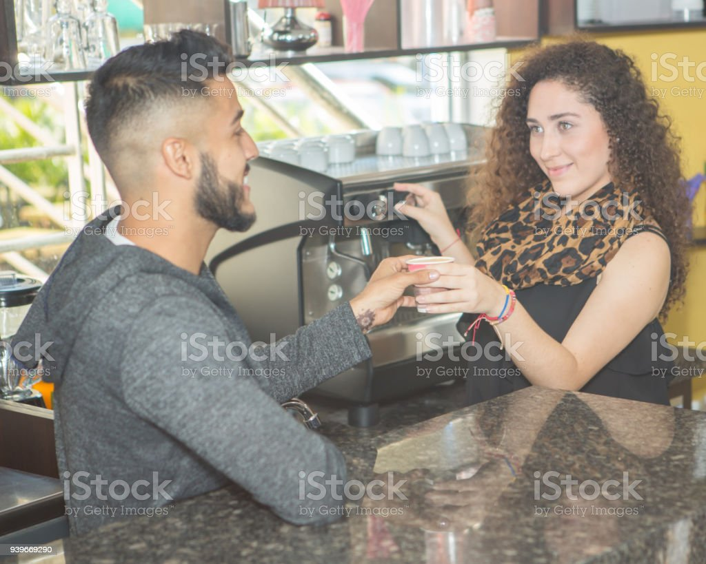 Lady small business employee serves a customer a cup of coffee.