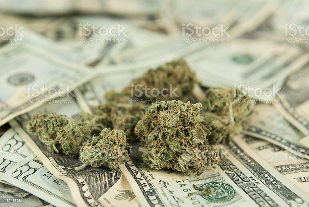 Retail Marijuana Concept Marijuana lying on twenty dollar bills symbolizing the now state run industry in the United States, while it still remains illegal at a federal level. American Twenty Dollar Bill Stock Photo