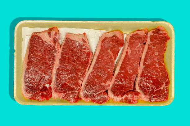 Retail packaging with five raw flat iron steaks Retail packaging with five raw flat iron steaks , oyster blade steaks or butlers steaks from the shoulder isolated on blue fruit carton stock pictures, royalty-free photos & images