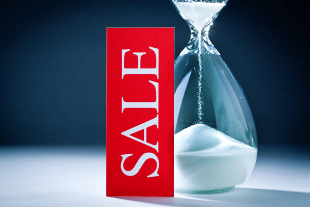 Retail Sale Deadline and Out of Time for Shopping: Sand Timer Hourglass and Sale Sign stock photo
