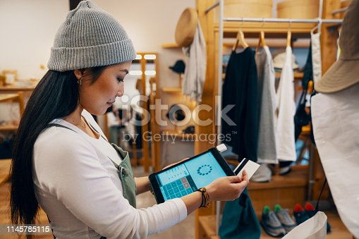Retail shop clerk taking a mobile credit card payment on a digital tablet in a clothing boutique in Japan