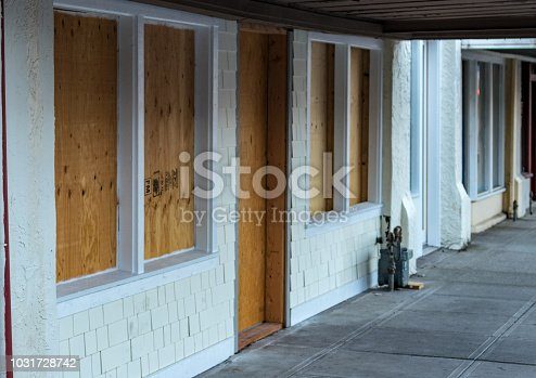 Retail storefront closed and boarded up with plywood