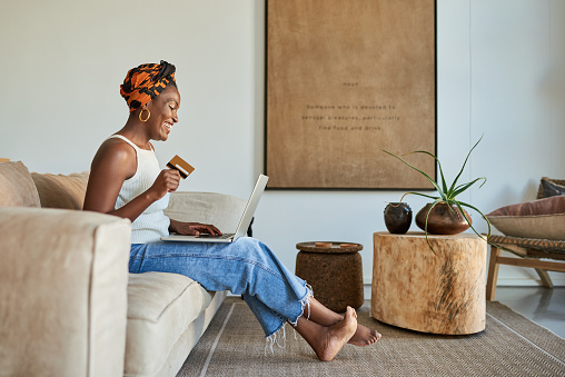 Shot of a young woman using a credit card and laptop on the sofa at home