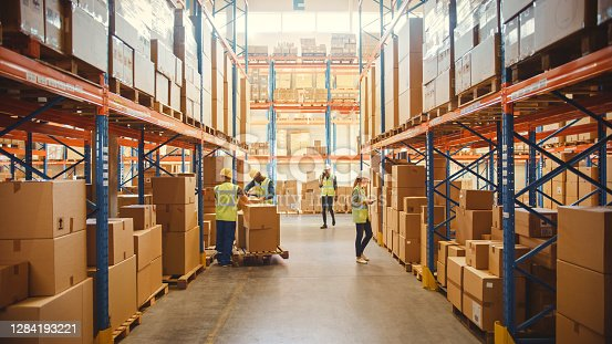 istock Retail Warehouse full of Shelves with Goods in Cardboard Boxes, Workers Scan and Sort Packages, Move Inventory with Pallet Trucks and Forklifts. Product Distribution Delivery Center. 1284193221