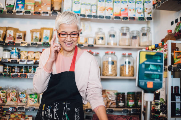 Retail woman using mobile phone at the healthy food store stock photo