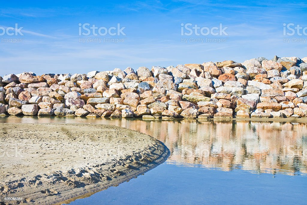 Retaining breakwater wall built with stone boulders stock photo