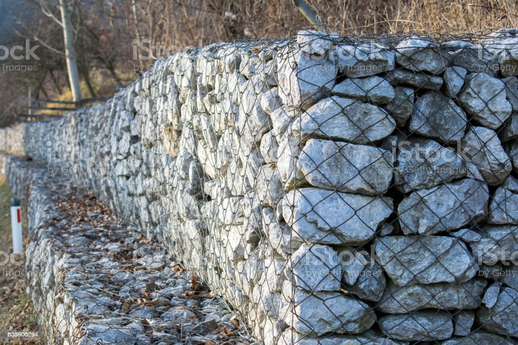 Retaining stone wall next to the road.Gabion wall. stock photo