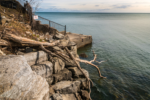 Retaining wall and pier with ducks, fallen tree, private property sign, fence running to waters edge and vast body of water. copy space