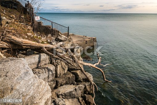 Heavy stone waterfront retaining wall, view of private property signage and rocky hillside with fallen tree and lake.