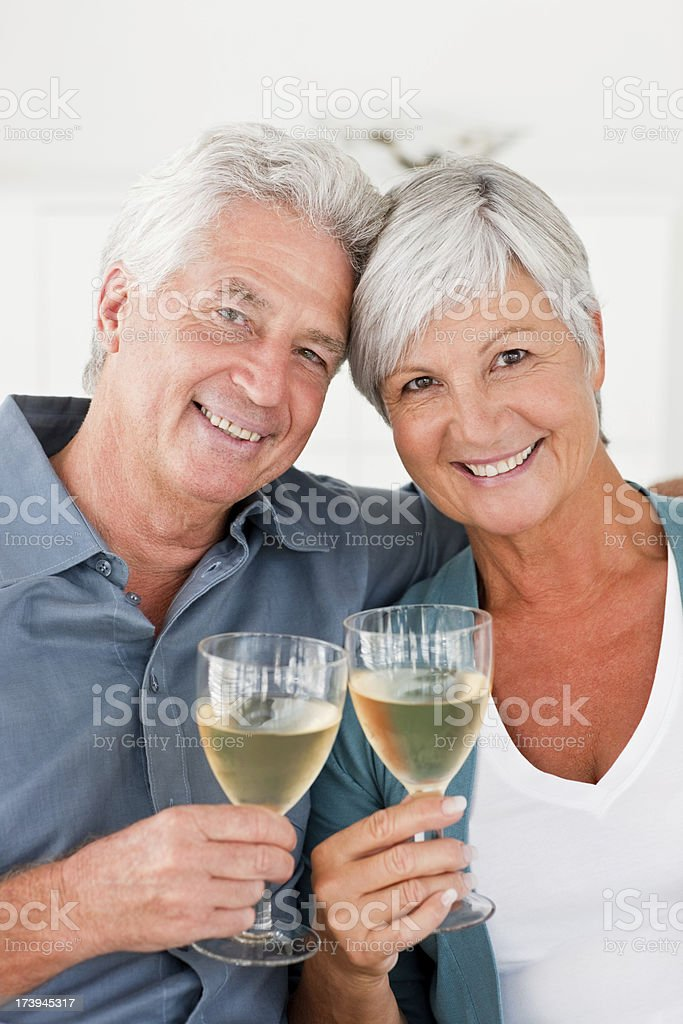 Retired couple enjoying a glass of champagne royalty-free stock photo