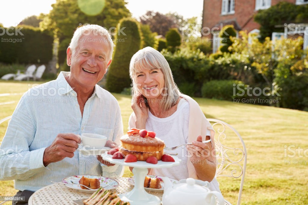 Retired Couple Enjoying Afternoon Tea In Garden At Home стоковое фото