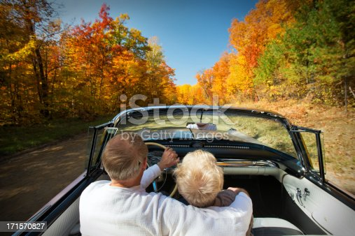 Retired couple enjoying a mid-day drive in a pink convertible on a beautiful Autumn day.