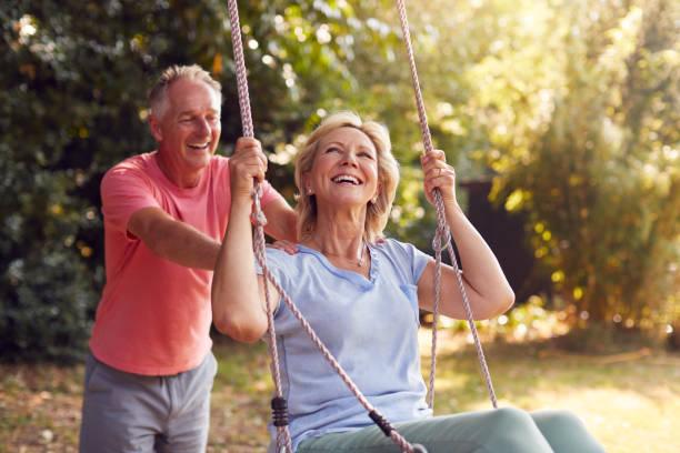 Retired Couple Having Fun With Man Pushing Woman On Garden Swing stock photo