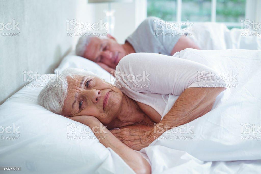 Couple de retraités de détente sur lit photo libre de droits