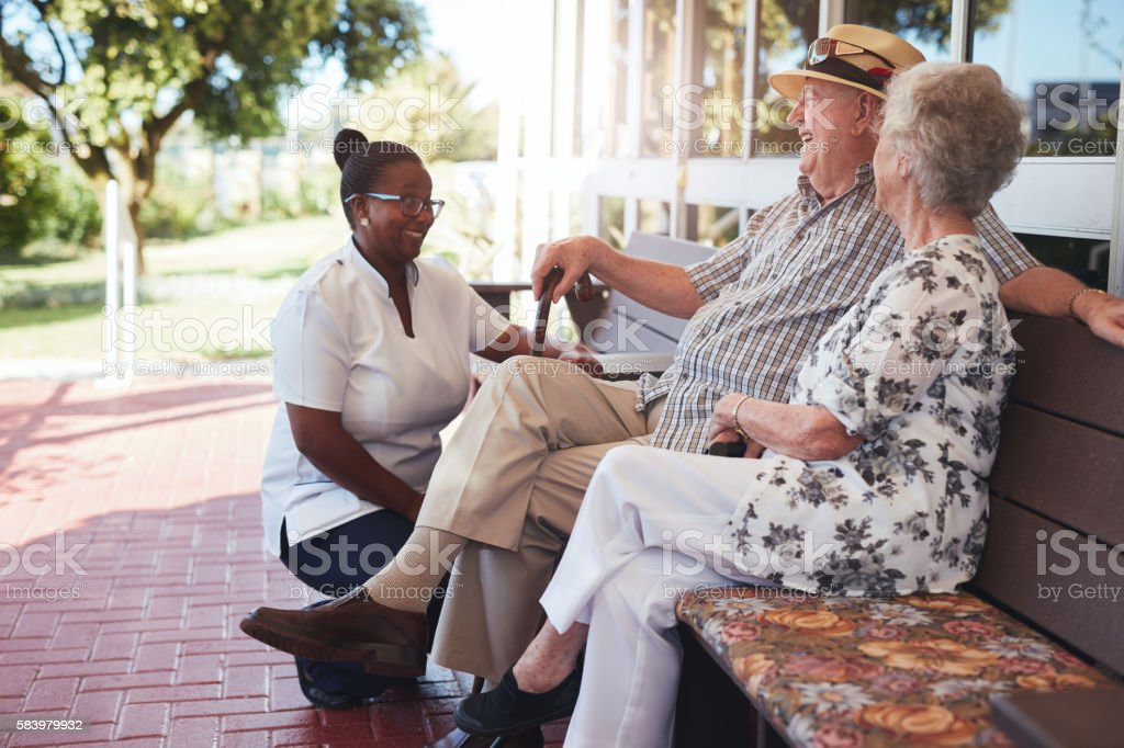 Retired couple relaxing outdoors with female caregiver stock photo