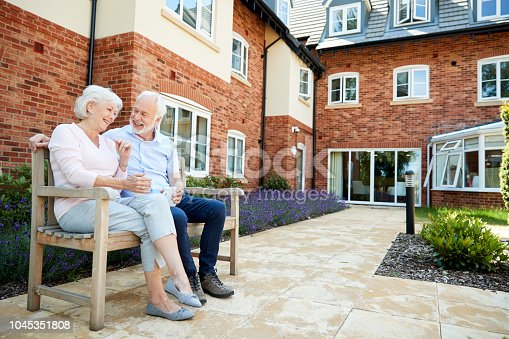 istock Retired Couple Sitting On Bench With Hot Drink In Assisted Living Facility 1045351808