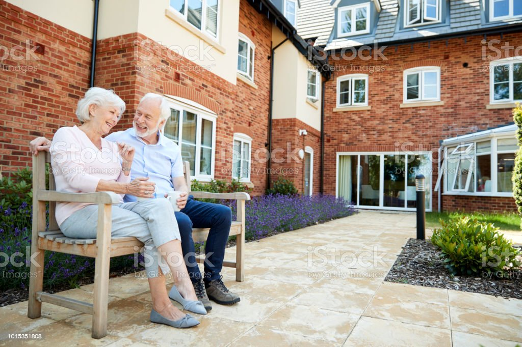 Retired Couple Sitting On Bench With Hot Drink In Assisted Living Facility stock photo