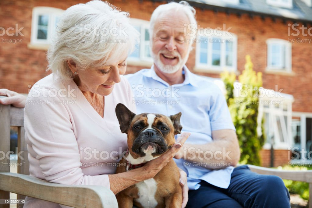 Retired Couple Sitting On Bench With Pet French Bulldog In Assisted Living Facility стоковое фото