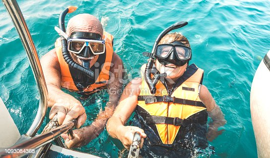 istock Retired couple taking happy selfie in tropical sea excursion with life vests and snorkel masks - Boat trip snorkeling in exotic scenarios on active elderly and senior travel concept around world 1093084368