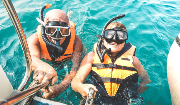 Retired couple taking happy selfie in tropical sea excursion with life vests and snorkel masks - Boat trip snorkeling in exotic scenarios on active elderly and senior travel concept around world Retired couple taking happy selfie in tropical sea excursion with life vests and snorkel masks - Boat trip snorkeling in exotic scenarios on active elderly and senior travel concept around world snorkel stock pictures, royalty-free photos & images