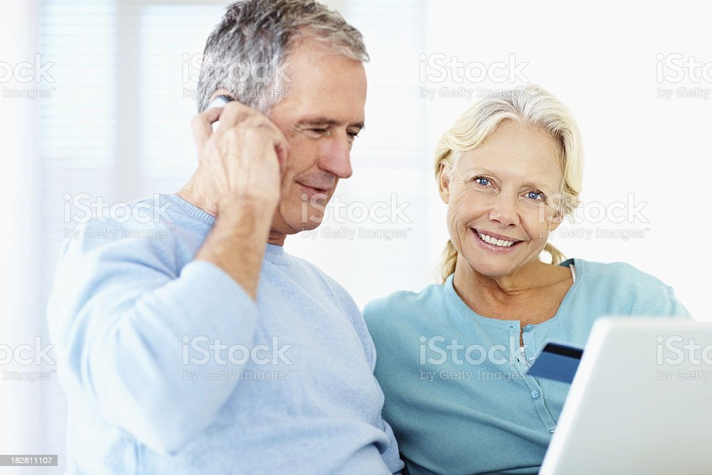 Retired couple using credit card to shop online royalty-free stock photo