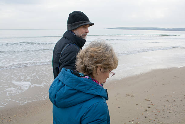 Retired couple walking on the beach stock photo