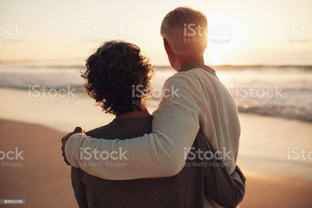 Retired couple watching amazing sunset stock photo