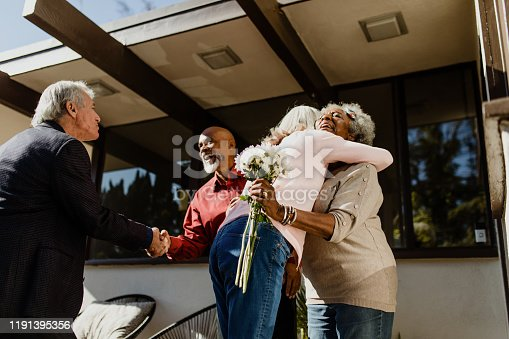 Low angle view of retired friends greeting each other at front yard. Smiling senior women embracing by men giving handshake. They are standing outside house on sunny day.