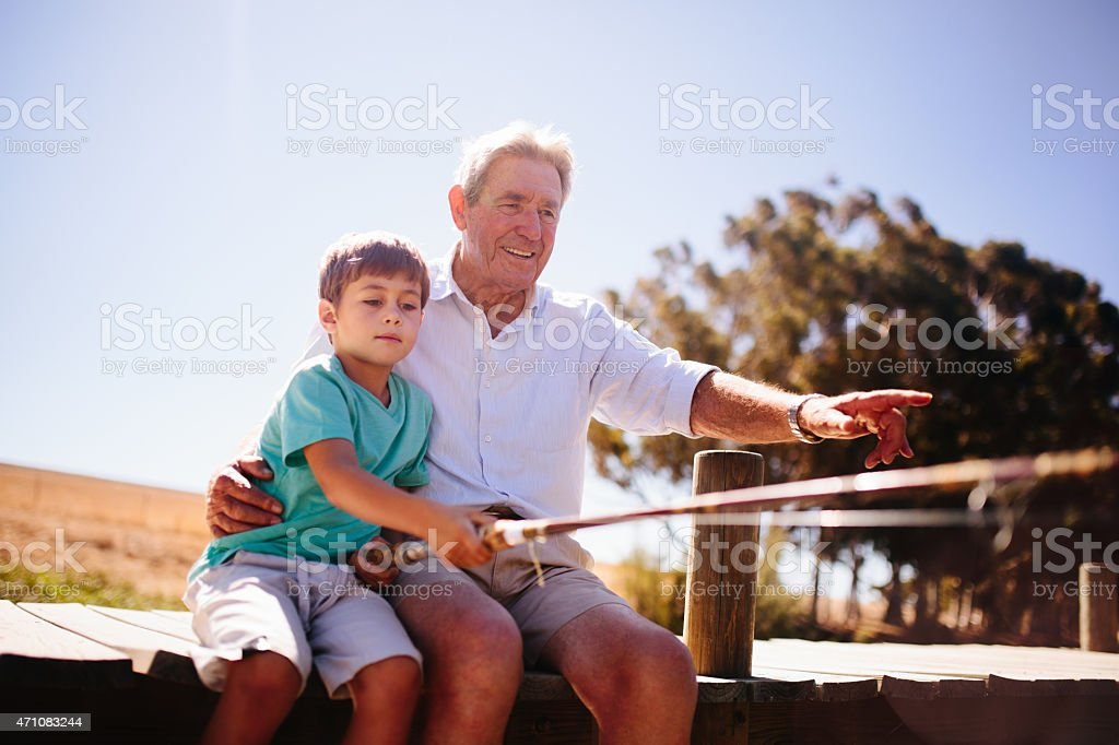 Retired grandfather teaching his grandson to fish stock photo