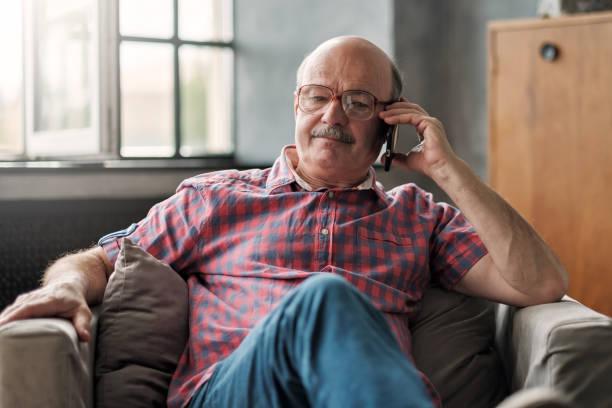 Retired hispanic man talking on phone sitting at living room. stock photo