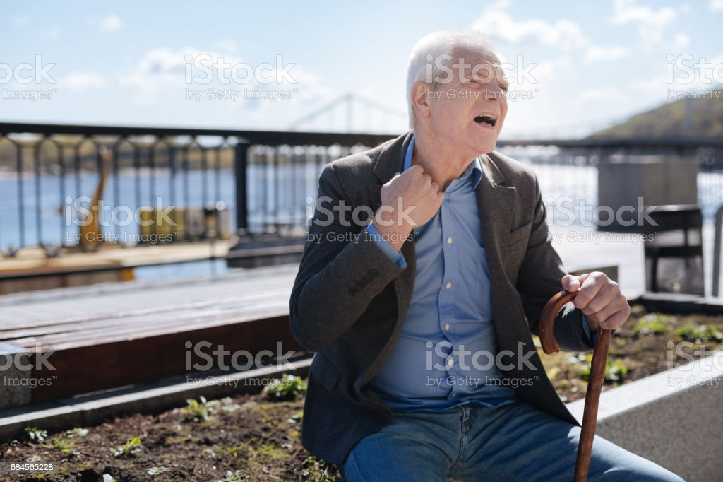 Retired man gasping on the promenade stock photo